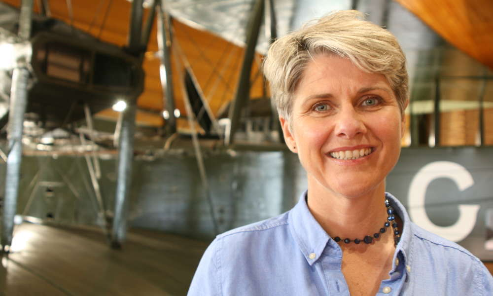 ​Sunday Mail columnist and author Lainie Anderson stands in front of the Vickers Vimy - the same open cockpit biplane that won the 1919 Great Air Race and the feature of her book 'Long Flight Home'.