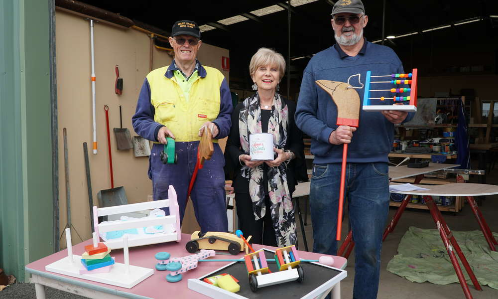 Men's Shed members Ian Bond and Peter Heness presented City of Mount Gambier Mayor Lynette Martin with 100 handcrafted wooden toys for distribution as part of the Mount Gambier Community Mayor's Christmas Appeal.