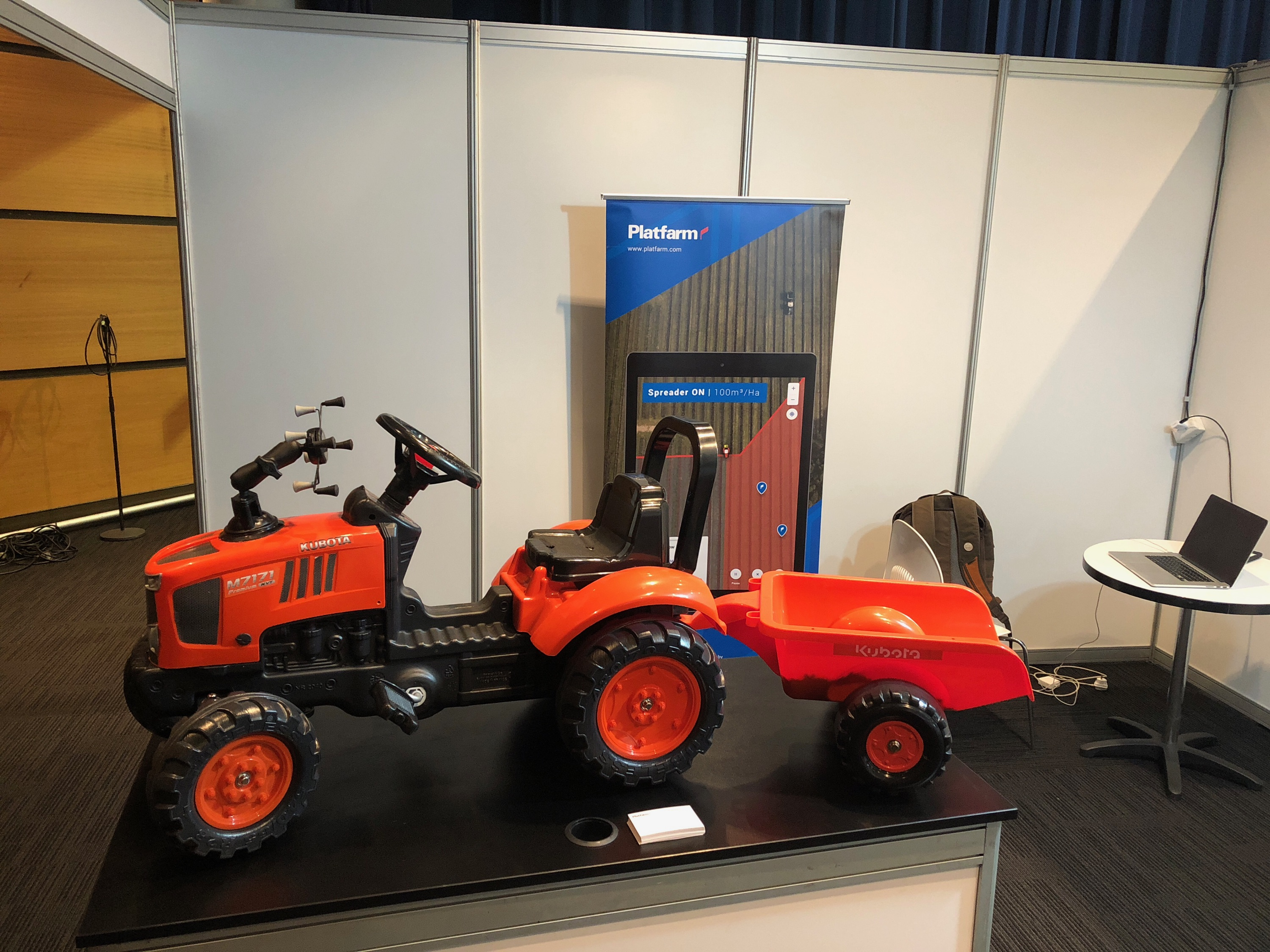 red mini tractor with demonstration platform device holder
