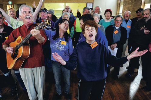 Spirit of the Streets Choir founder Bernard Carney and member Wendy Goldsmith (foreground) sing Put a Little Love in Your Heart with fellow choir members. Picture: Marcus Whisson www.communitypix.com.au d402956