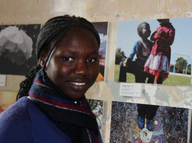 Akudut Manuer with her photo of a boy and girl that is on display in the Restoring Hope Art Exhibition.