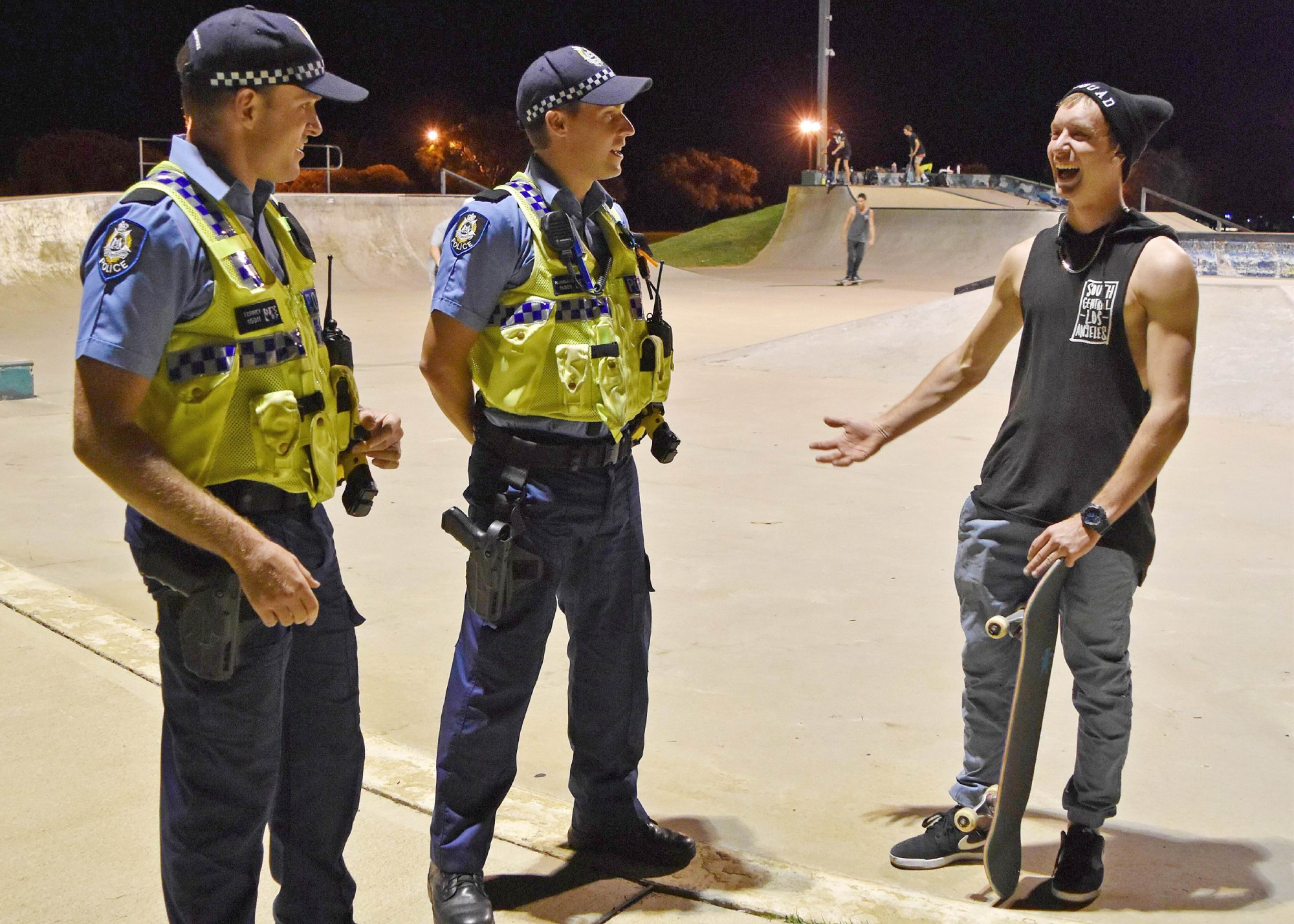 Officer Brad Terrey, Officer Rob Hubbard and local skater Koby Atkinson share a laugh.