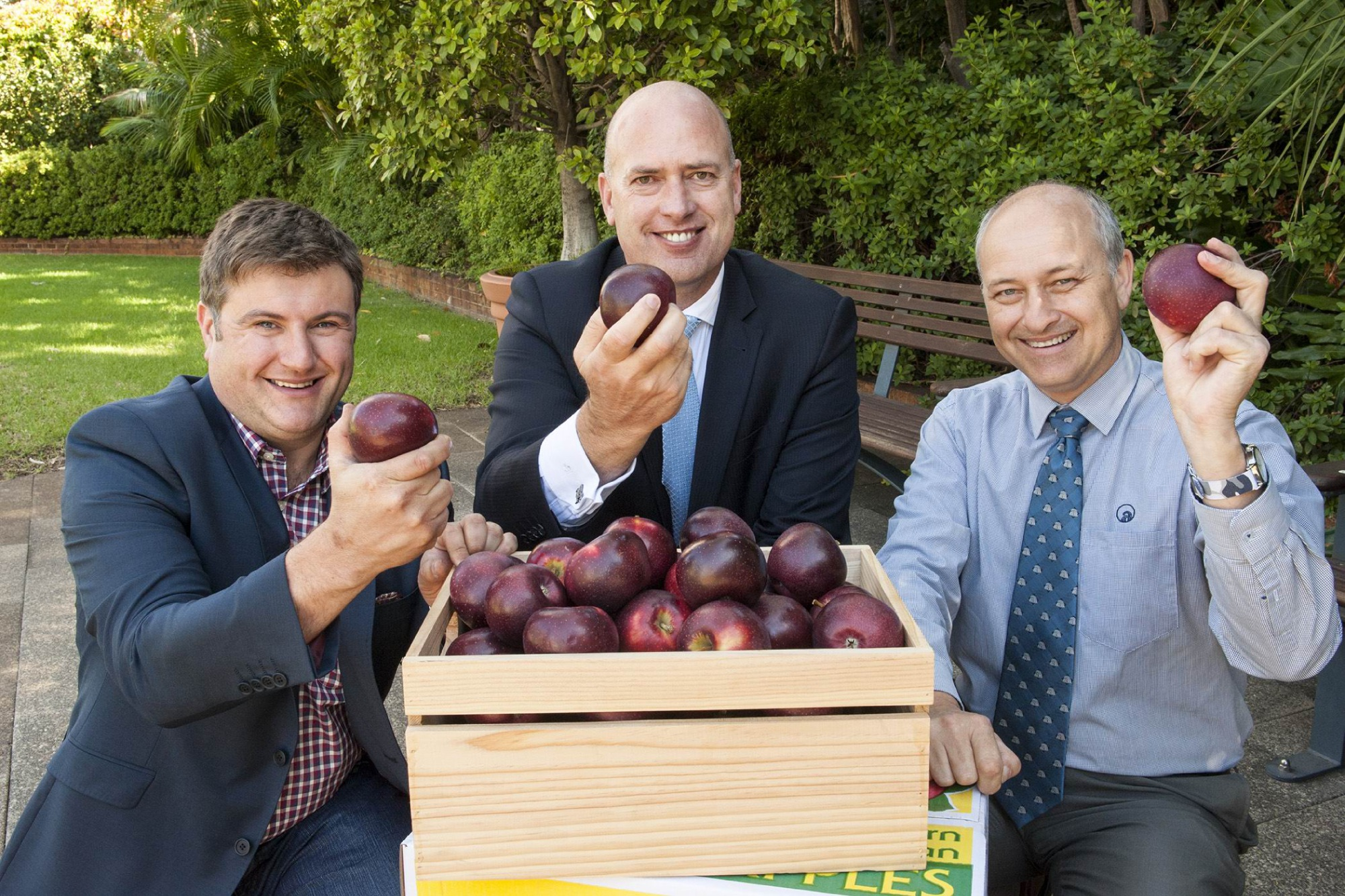 WA grower Mario Casotti, Agriculture and Food Minister Dean Nalder and Department of Agriculture and Food Horticulture Director David Windsor with the new locally bred apple Bravo, distinguished by its rich burgundy colour.