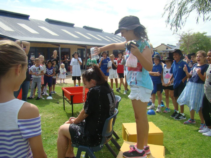 Lauren Willis pouring water on Year 6 teacher Samantha Rodgers.