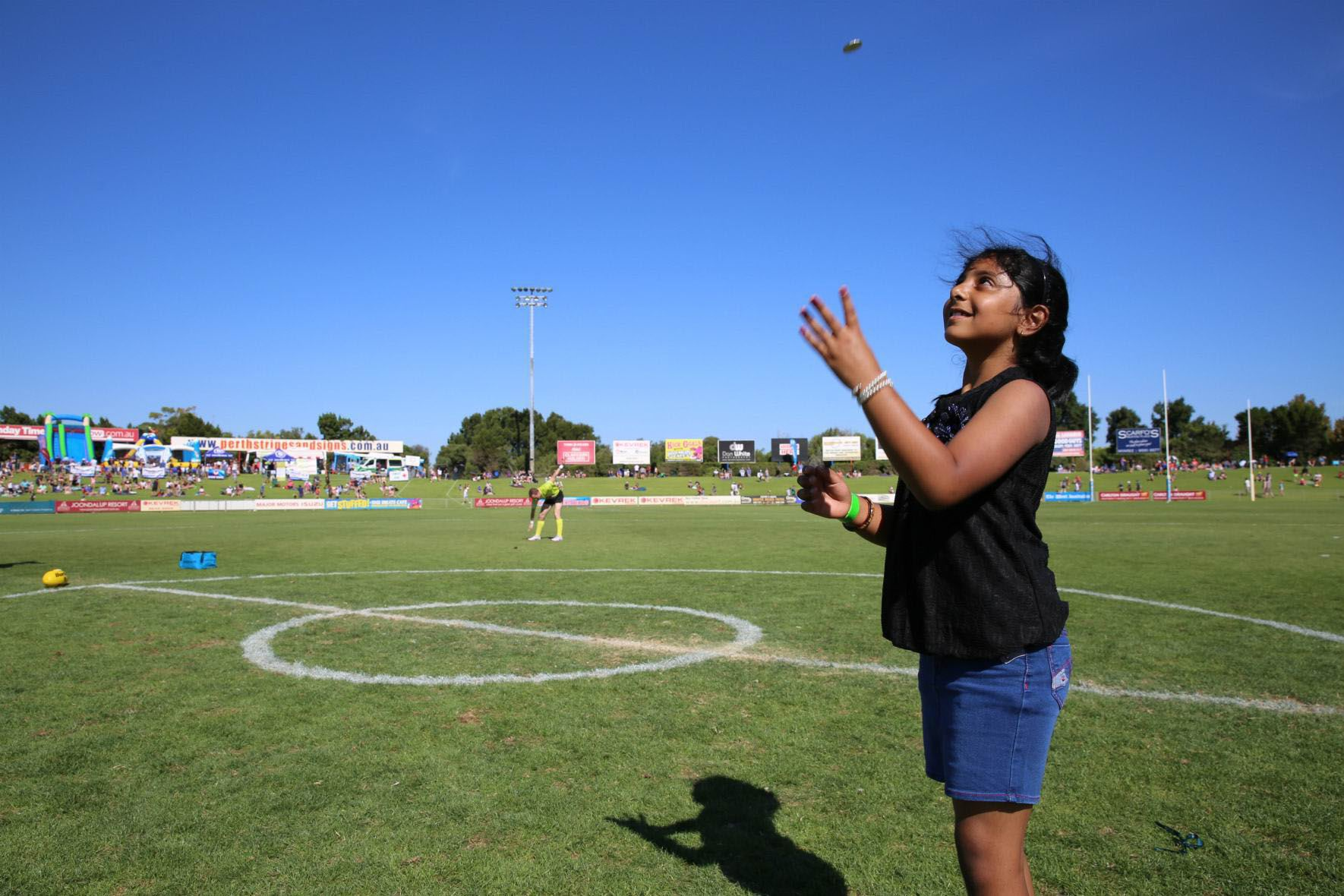 Indian migrant Evana George tosses the coin before the match after becoming an Australian citizen. Picture: Chris Kershaw