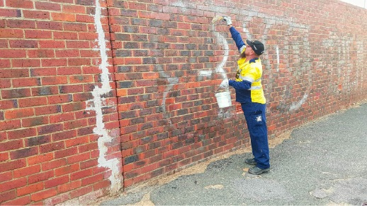 Graffiti removalist Michael Hood removing tags from a Midland laneway.