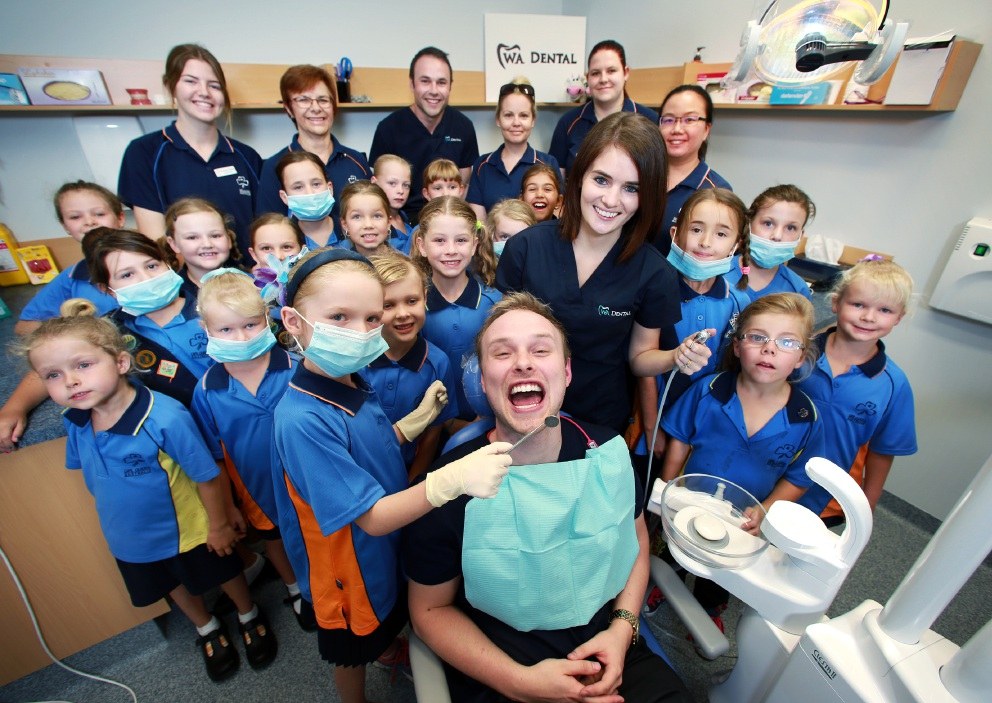 Ava Smith (8), in foreground, checking out the teeth of Dr Marc Nalder, surrounded by Dr Lesley Moffat, members of the Ellenbrook Sunshine Girl Guides and staff at WA Dental in Ellenbrook.   d451455
