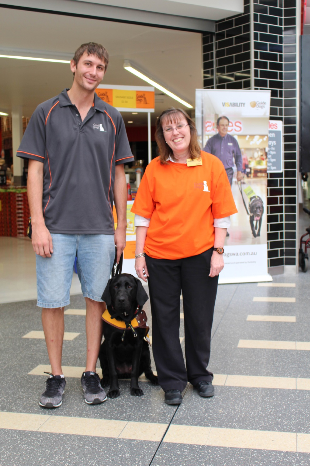 Guide Dogs WA |representative Josh Crawford, Coles staff member Andrea Carde and trainee guide dog Poppy.