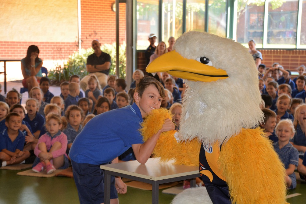 Year 4 student James Townsend arm-wrestles Rick the Rock during the Eagles in the Community visit to Woodbridge Primary School