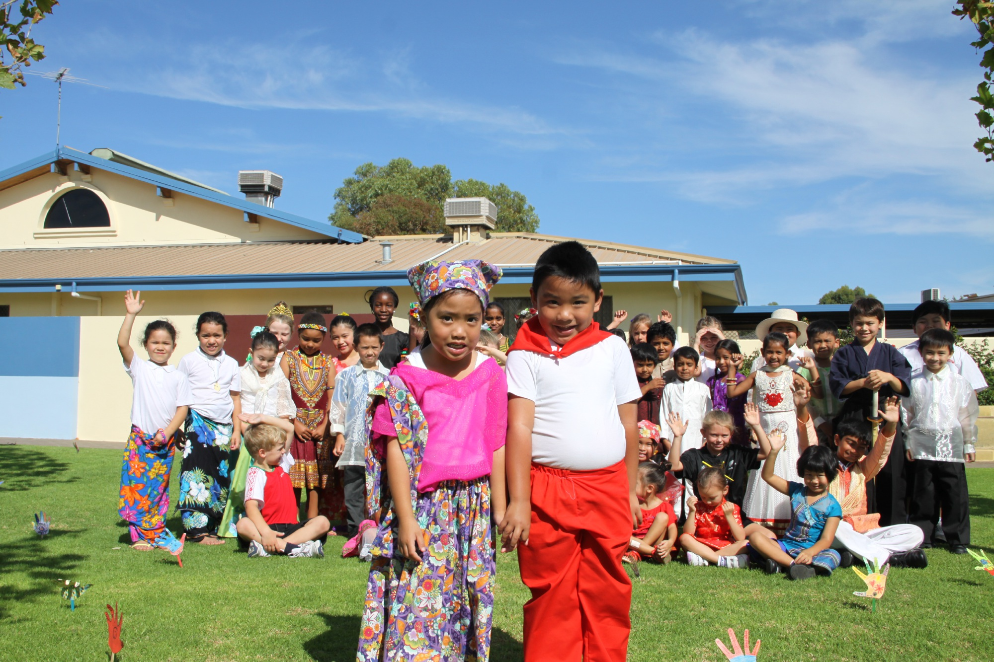 Five-year-olds Luis and Sophia Villanueva wearing traditional dress from the Philippines stand in front of other students wearing their traditional dress. Picture: Gabrielle Jeffery