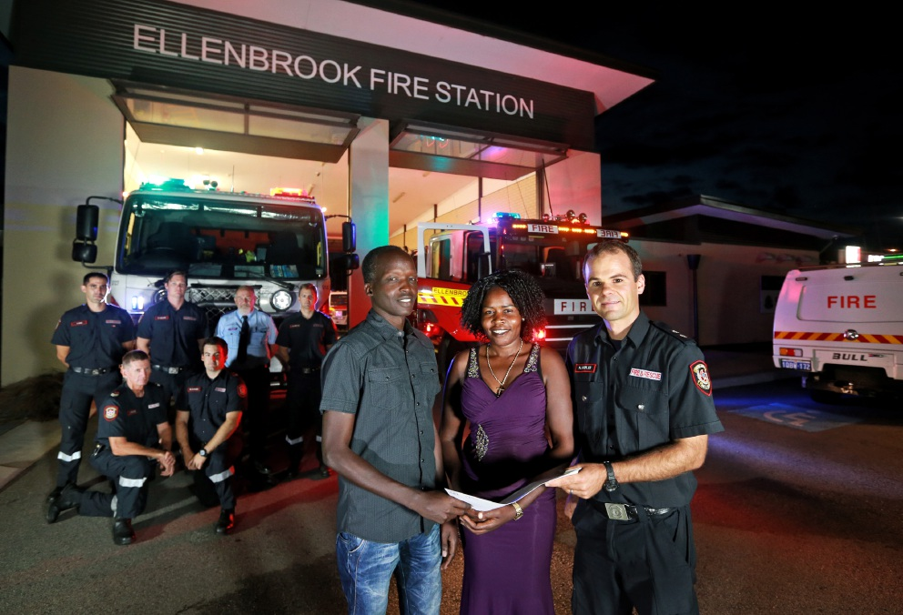 Bandak Bak and Nyapuka Nyuon receive the money from Ellenbrook Fire Station officer Hannes Hoefler while other firefighters look on. Picture: David Baylis www.communitypix.com.au   d451513