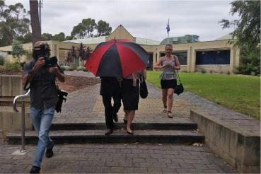 The accused Mandurah teacher leaves the Mandurah Magistrates Court under cover of an umbrella. Picture: Rachel Fenner