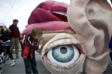 A curious child gets up close to the Snuff Puppets' giant eye, ear and mouth.