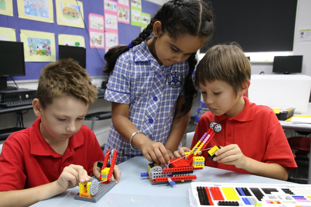 Students Oliver Fenwick, Meher Lobana, and Jien McKenzie learn about scientific principles using Lego.