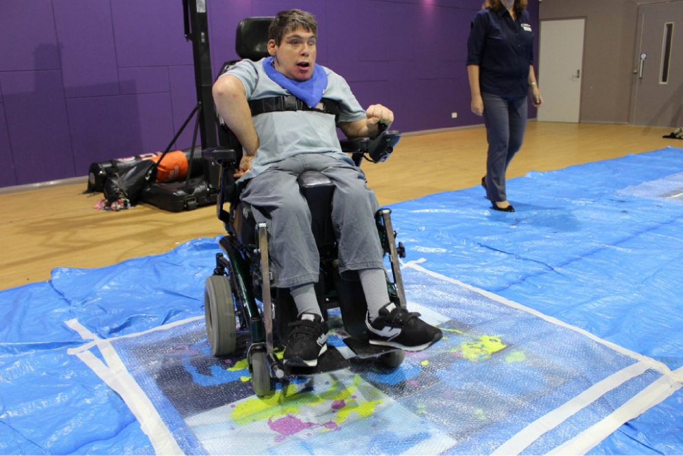 Andrew Murray steers his wheelchair over paint and tiles to create a print.