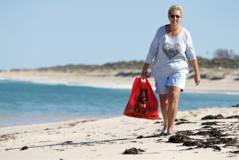 Clare Sharp collects litter from the beach in Yanchep. Picture: Martin Kennealey www.communitypix.com.au   d450476