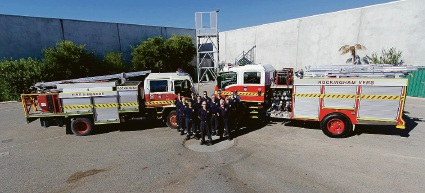 Captain Andrew Munro  (centre) and volunteers with the new truck on the right and the unit's old truck on the left.