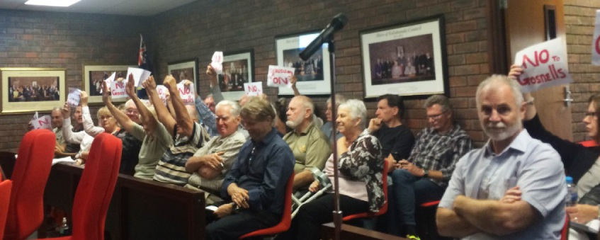 Ratepayers opposed to a proposal for Wattle Grove to secede to City of Gosnells hold up signs.