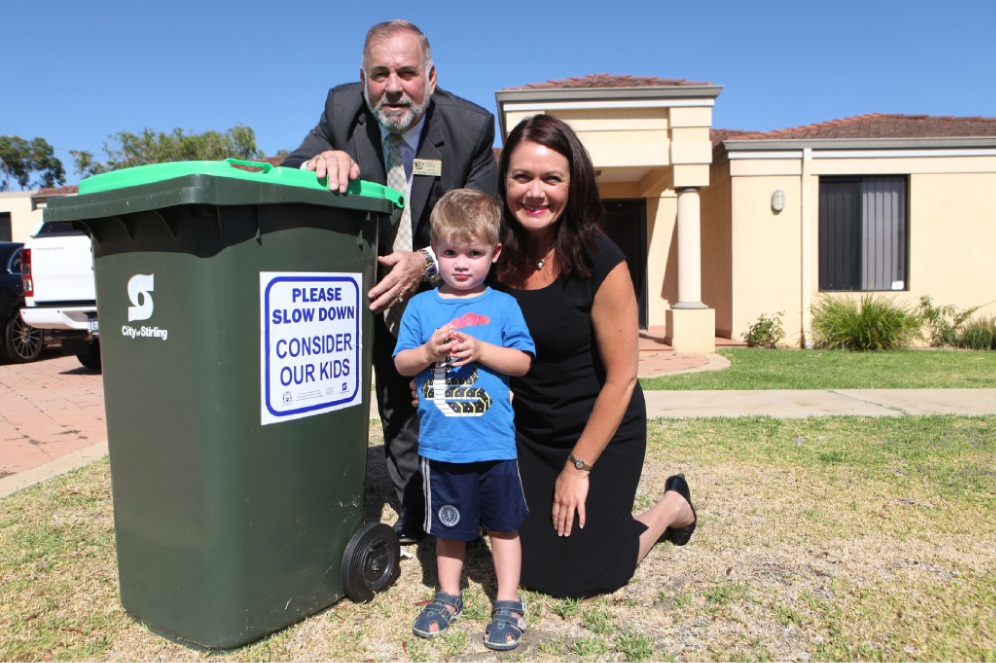 Stirling Mayor Giovanni Italiano, Road Safety Minister Liza Harvey and Connor Pope with one of the bin stickers.