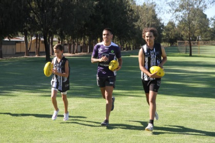 Michael Walters (centre) trains with some youths ahead of the Nicky Winmar Carnival.