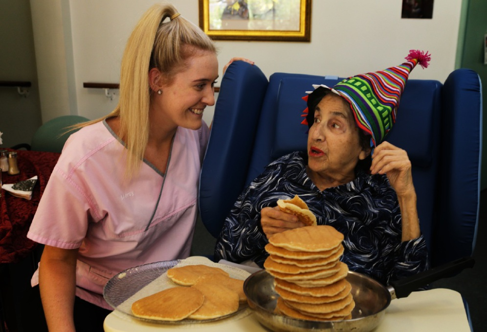 Carer Alex Fleming with Pina Torchiaro and a pile of pancakes. Picture: Martin Kennealey www.communitypix.com.au   d449466