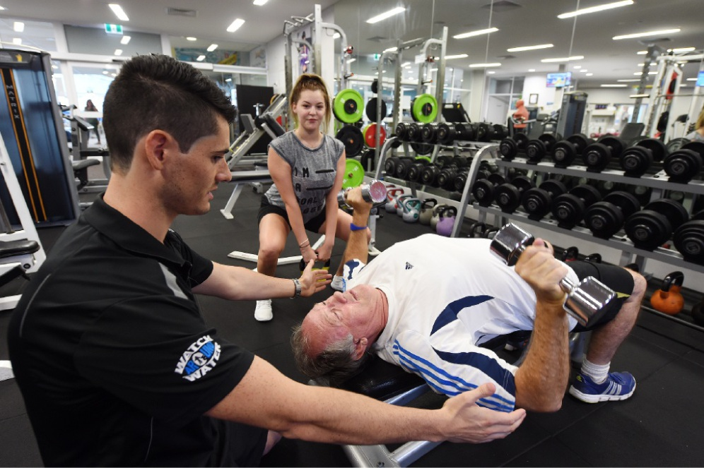 Gym instructor and personal trainer Tim Iffla guides Jim Burke on lifting weights, watched by Sarah Lavell. Picture: Jon Hewson d448920