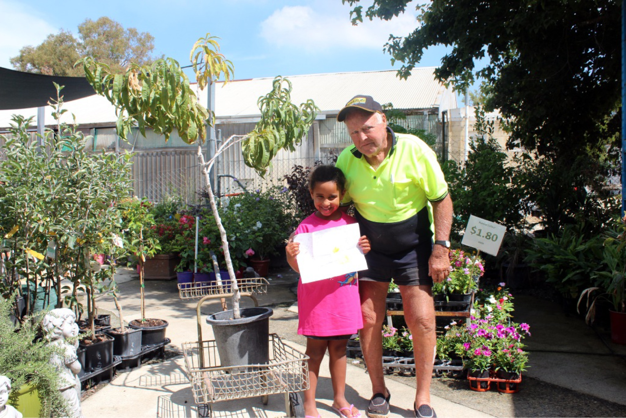 Annika Klaus, with Kearns Garden and Hardware employee Harry Tebbutt, is all smiles after her stolen peach tree was replaced by a new one donated by the store.