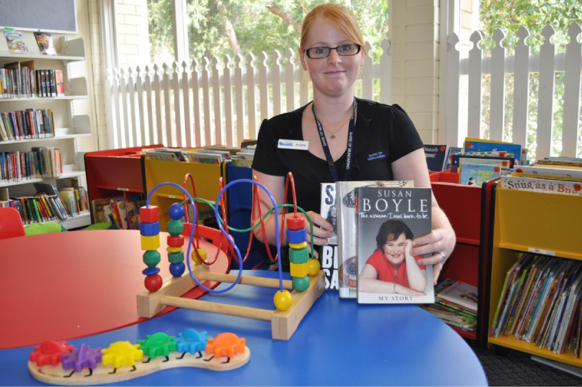 Senior library officer Amanda Rowe gets read for the toy and book sale.