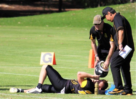 Raiders head coach Lane Honda and medical officer Dan Jolley attend to Damien Donaldson after his injury. Picture: Andrea Sampson