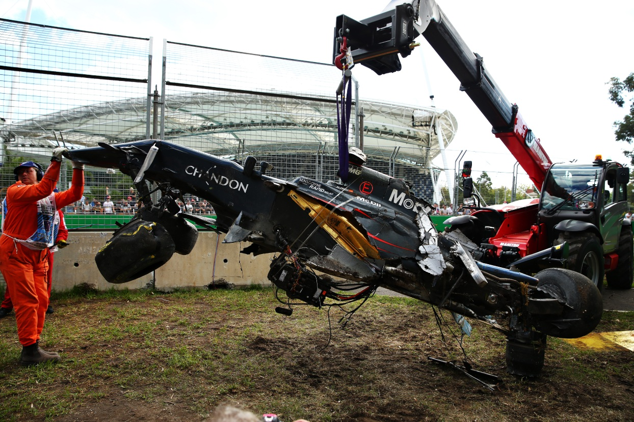 After the crash: Fernando Alonso's car is pulled from the side of the track after his chilling 280km/h crash. Picture: Robert Cianflone/Getty Images