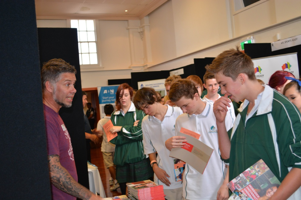 A Murdoch University careers advisor hands out information to students from Lesmurdie Senior High School.
