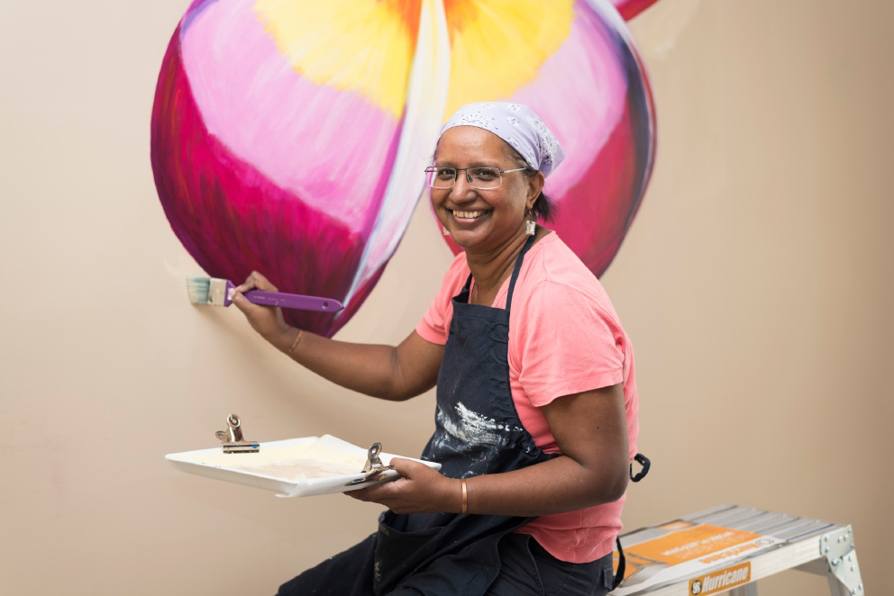 Jane Dacruz painting a frangipani mural at the dementia care centre.