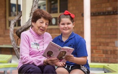 Volunteer mentor Kay Leek spends time with student Asha Keynes (8).
