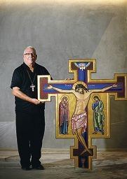 Grace Anglican Church parish priest David Wood with the new font and next to the crucifix by artist Marice Sariola, which will hang above the church altar. d395994