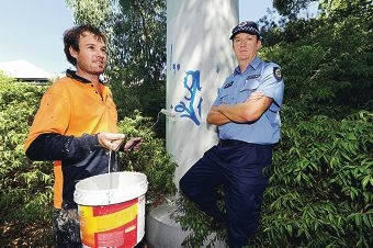 Graffiti Systems Australia removalist Justin Willett and Wembley Police Station officer-in-charge Senior Sergeant Jade Smith prepare to remove graffiti from a pillar.d397140