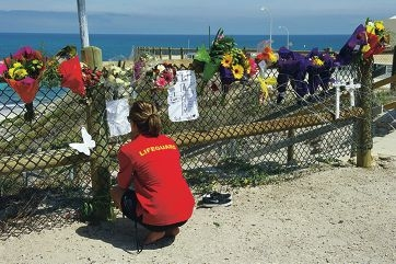 A lifeguard looks at floral tributes, which include two crosses (far right) representing the two lives lost at Clayton's beach. Picture: Emma Reeves www.communitypix.com.au d397873