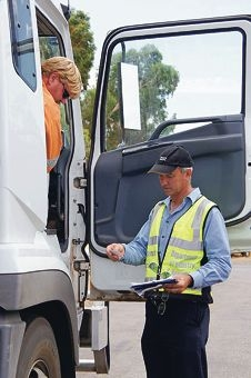 A DMP officer interviews a truck driver at the Northam roadblock.