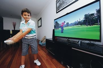 Golf pro in the making? Terry Hatzis hits a drive, Tiger Woods style, on his Wii console.