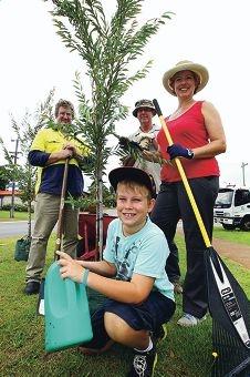 Francis Waters, Dave Hutchison, Elana Walsh-Negus and Jordan Negus (9) prepare a street tree for planting.