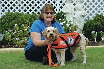 Falcon woman Sharlene Thomas with her new companion Gino, a Lions hearing dog.
