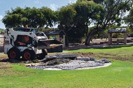 A bobcat at work removing the Aboriginal mosaic at a the beach reserve...