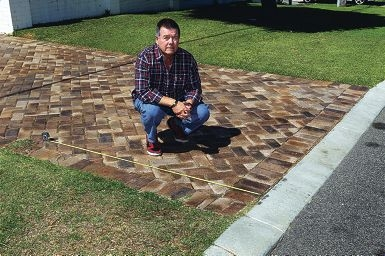 Scarborough resident Kevin Kenneally shows how much of his driveway would have to be ripped up to make way for a footpath. Picture: Dominique Menegaldo www.communitypix.com.au d398422