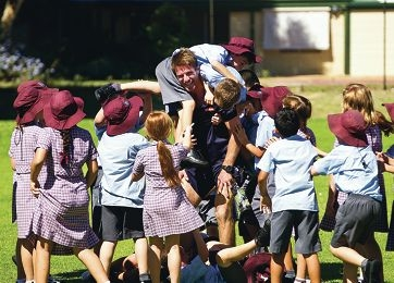Beau Waters is surrounded by students during his visit to St Maria Goretti's Primary School with team mates Luke Shuey and Ashley Smith.