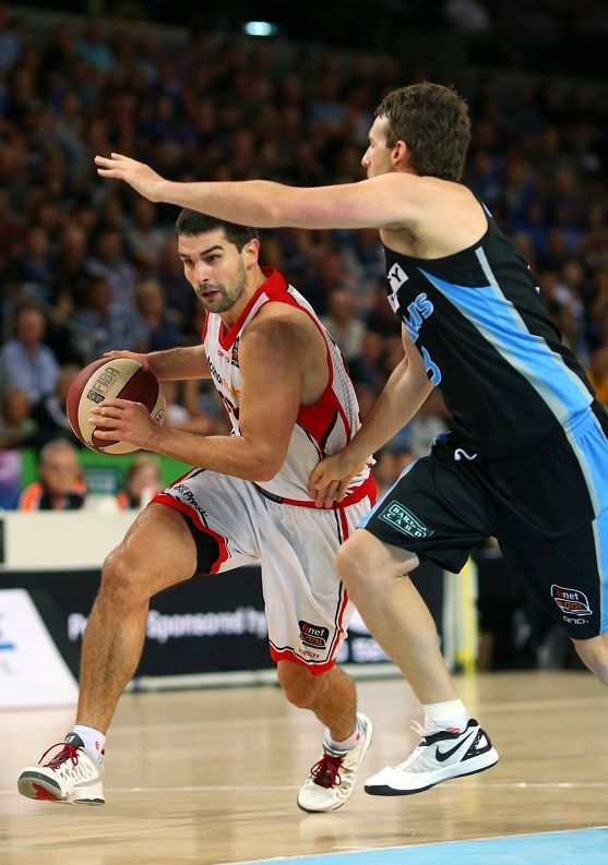 New Zealand Breakers' Corey Webster attempts to block Wildcats guard Kevin Lisch's run to the goal.