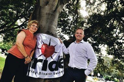 New Pride WA co-presidents Michelle Rigg and Daniel Smith with the Pride WA flag.
