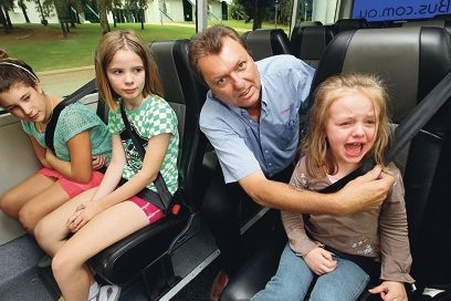 Dingo Bus Charters owner Andrew Reid shows seatbelts fitted to his buses are not one-size fits all for children as he buckles in Bianca Lack while Aari Jooste-Occhiuto and Maddison Lack look on.