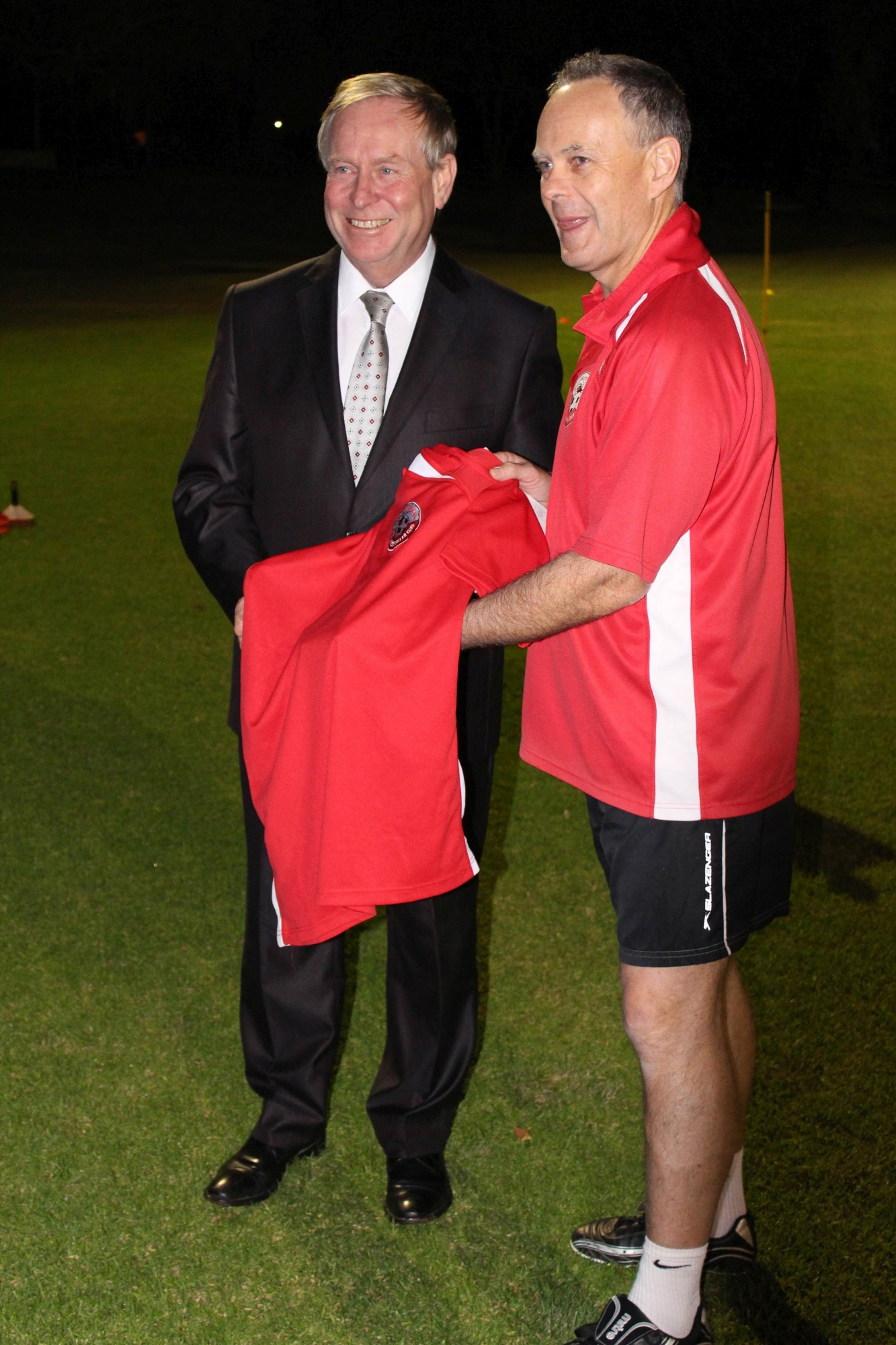 Club president Keith Anderson hands a jersey to the Premier.