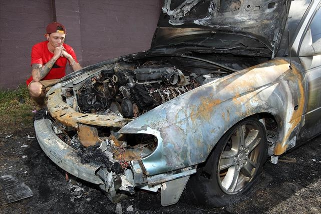 Up in smoke: Riley Gleeson with his burnt-out ute, which he had bought for $6000 just days earlier. Picture: Dominique Menegaldo d401798