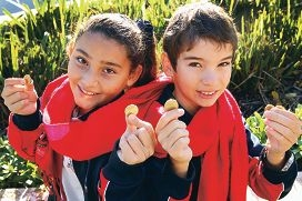 Year 6 students Fatima Arman Rad and Nikolas Keskic with their gold-coin donations. Picture: Marcelo Palacios d402625