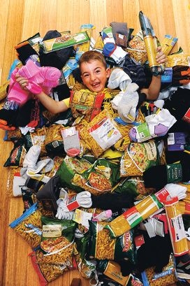Lachlan Quartermaine (9) surrounded by pasta and socks he is donating to a charity. Picture: Marcus Whisson www.communitypix.com.au d402839